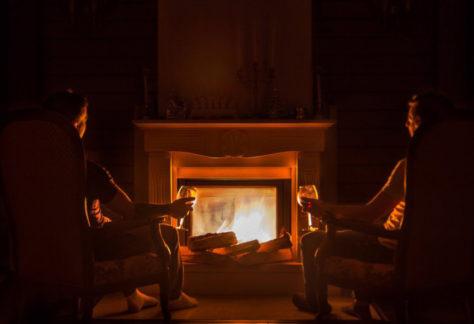 Zwei Personen sitzen vor Kamin mit Getränk